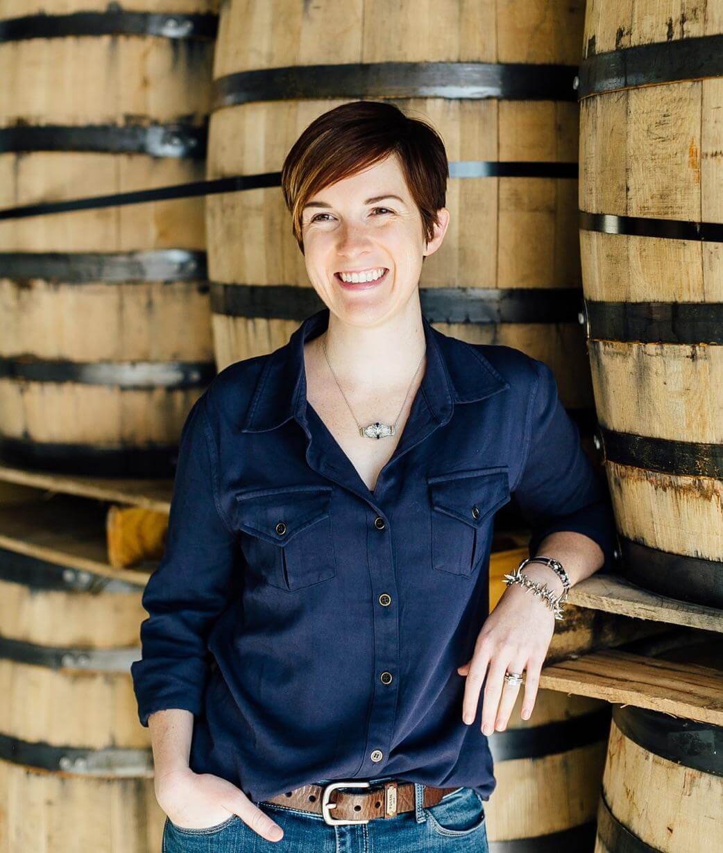 Master Distiller Alex Castle leaning on whiskey barrels and smiling