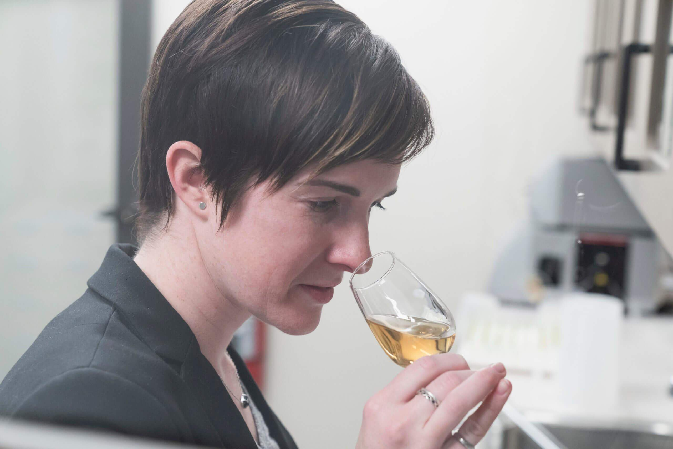 Alex Castle smelling a glass of whiskey in her lab