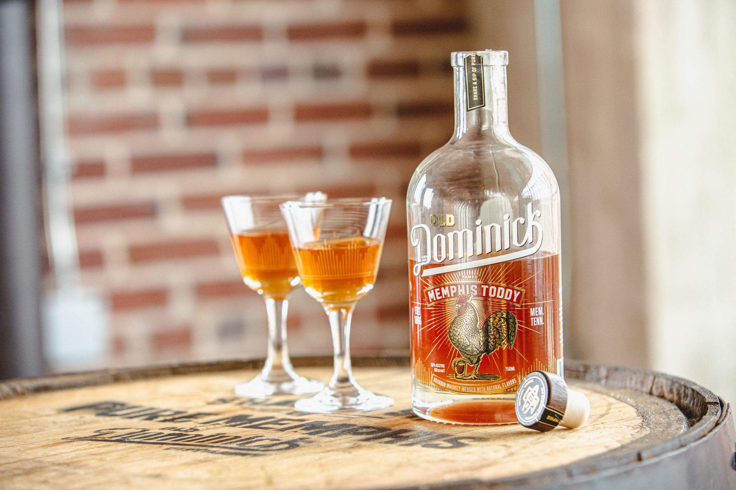 Old Dominick Memphis Toddy bottle and two glasses of toddy