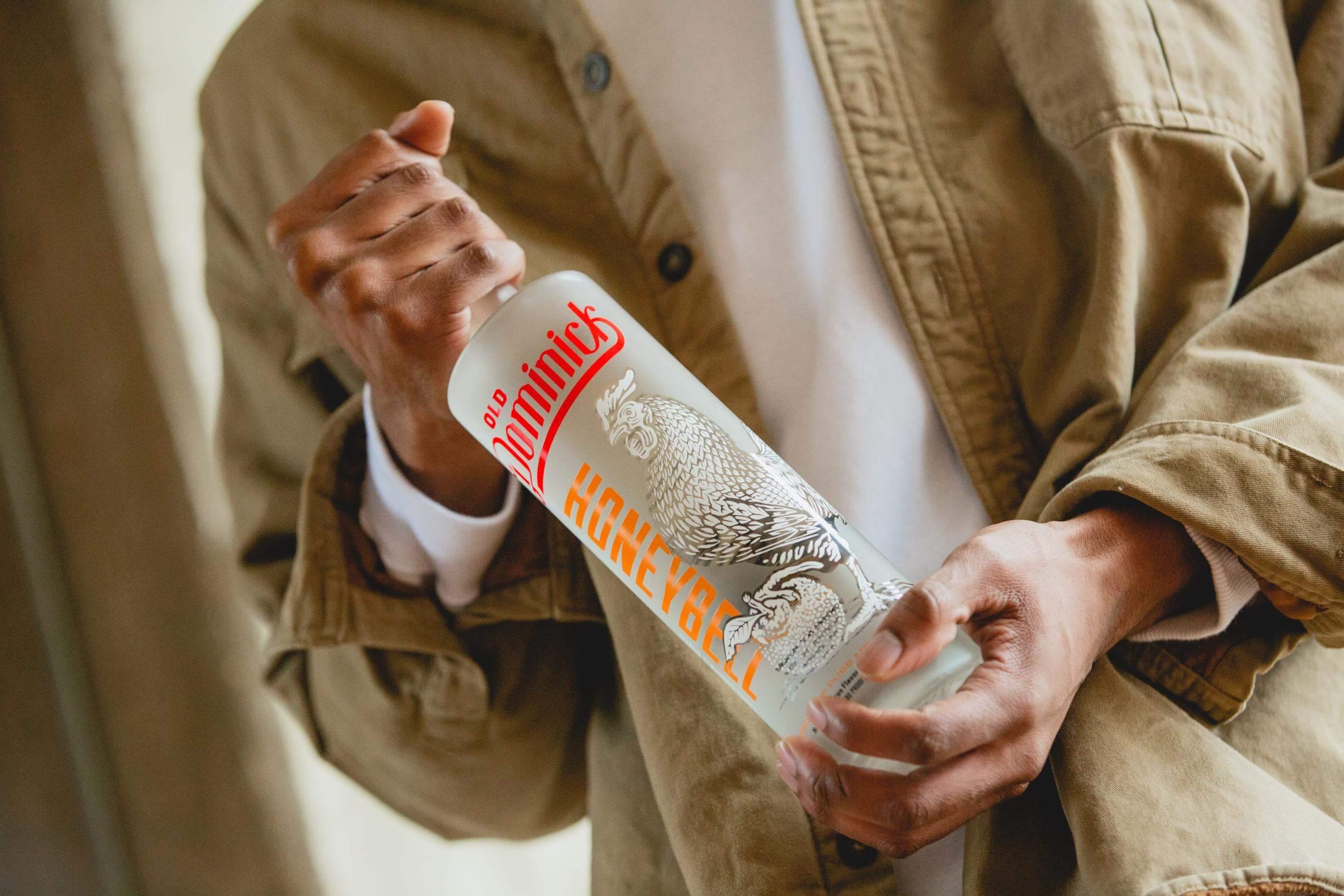 Man holding Honeybell Citrus Vodka bottle