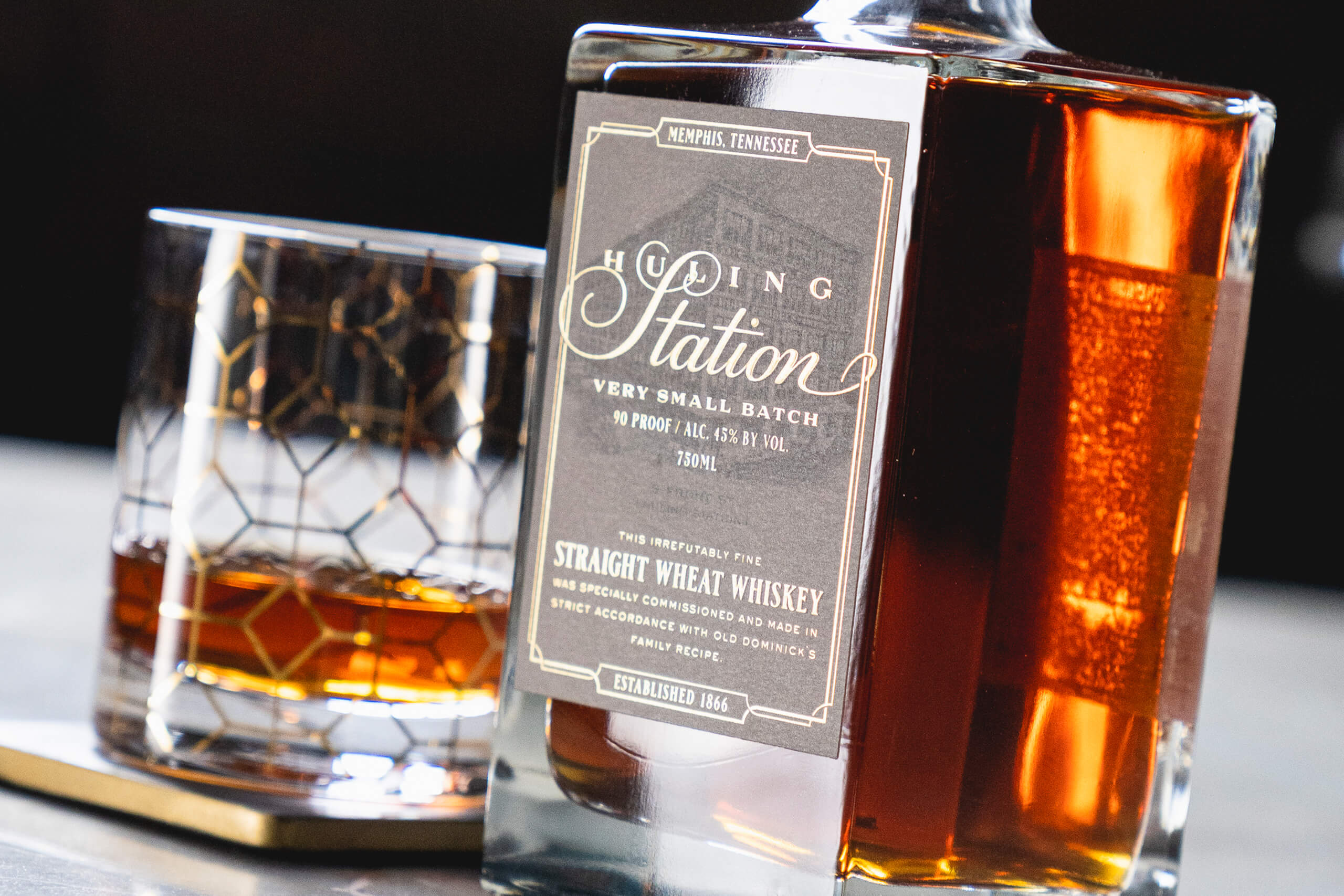 Huling Station Wheat Whiskey and a gold-trimmed glass of whiskey